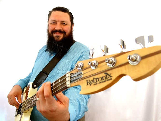 Photo of 251 Group founder Ryan Byrne wearing a light blue collared shirt while holding a bass guitar and smiling.